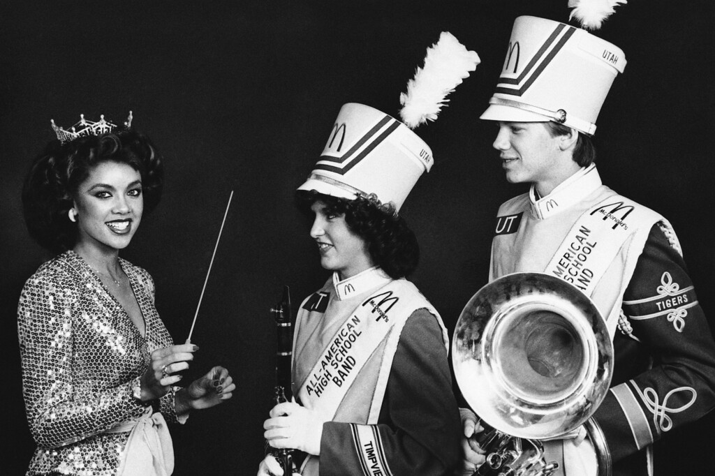 Description of . Miss America Vanessa Williams, joins two members of the 1983 McDonald's All-American High School Band in New York, Nov. 22, 1983, where they are preparing for their appearance in the Macy's Thanksgiving Day Parade. Leslie Crowley, second from left, and Jeff Hanson, right, both from Utah, are among the 104 high school musicians selected annually to participate in the band. (AP Photo)