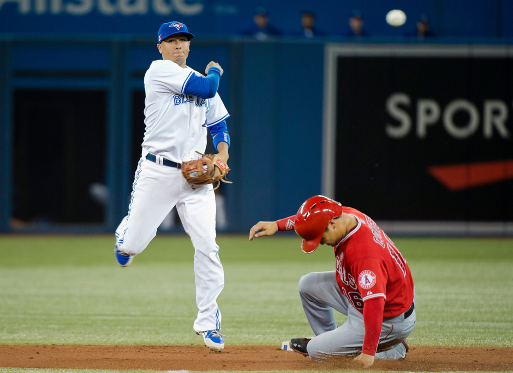 Description of . Toronto Blue Jays second baseman Ryan Goins, left, forces out Los Angeles Angels' Hank Conger, right, at second base then turns the double play over to first base to get out Angels' Grant Green during second-inning AL baseball game action in Toronto, Wednesday, Sept. 11, 2013. (AP Photo/The Canadian Press, Nathan Denette)