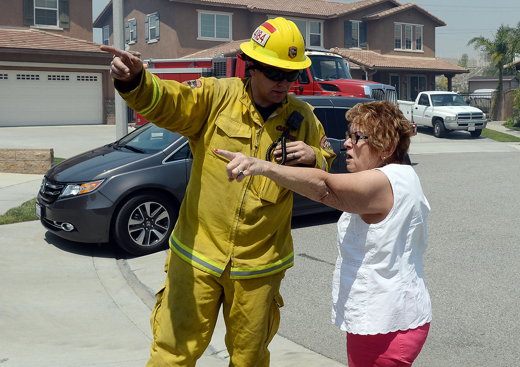 Description of . A resident speaks with a firefighter in Rancho Cucamonga Wednesday. Over 1,000 acres and over a 1,000 homes are under mandatory evacuation as the Etiwanda Fire burns in Rancho Cucamonga Wednesday April 30, 2014. Cause of the fire is unknown and is burning in areas which burned during the Grand Prix Fire in October 2003. (Will Lester/Inland Valley Daily Bulletin)