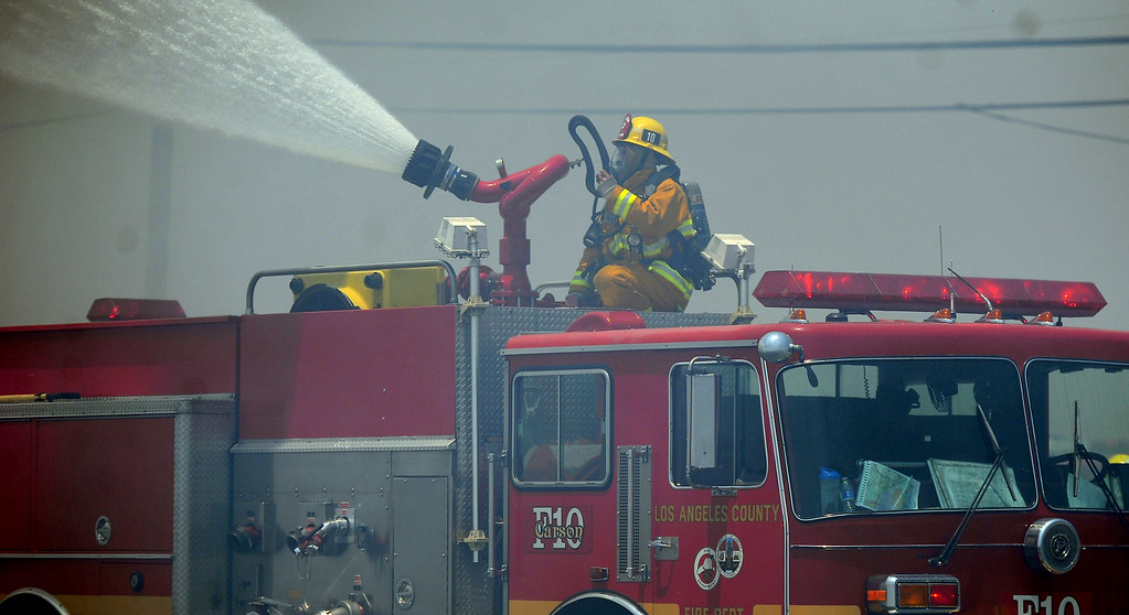 Description of . Los Angeles County firefighters from across the valley battle a 3-alarm fire at an abandoned warehouse near 9th Avenue and Clark Avenue on Tuesday, July 9, 2013 in City of Industry, Calif.  (Keith Birmingham/Pasadena Star-News)