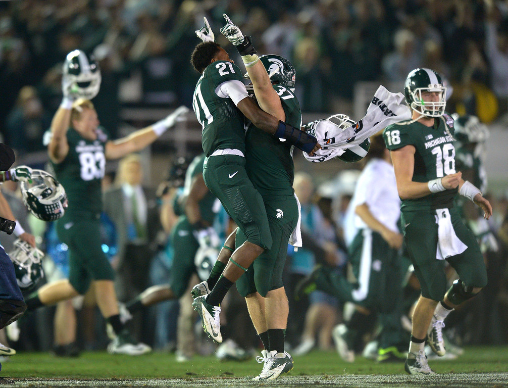 Description of . Michigan State celebrates after beating Stanford 24-20 at the Rose Bowl, Wednesday, January 1, 2014. (Photo by Michael Owen Baker/L.A. Daily News)