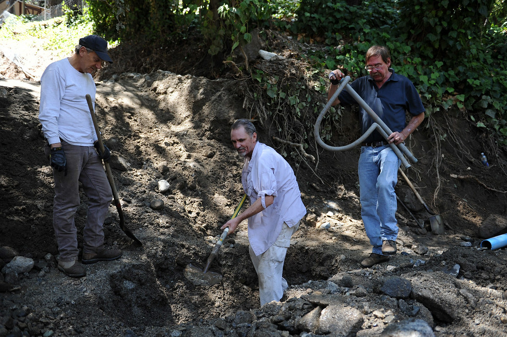 Description of . Local landowners and shareholders of the Forest Park Mutual Water Company repair a water line after Sunday's storm caused flooding on Monday, August 4, 2014 in Forest Falls, Ca. (Micah Escamilla/San Bernardino Sun)