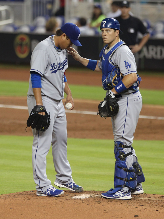 Description of . Pitcher Hyun-Jin Ryu #99 of the Los Angeles Dodgers chats with Catcher A.J. Ellis #17 (R) against the Miami Marlins at Marlins Park on August 19, 2013 in Miami, Florida.  Marlins won 6-2.   (Photo by Marc Serota/Getty Images)