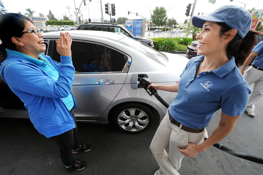 Description of . Tamara Torres, Honda Helpful Team member, pumping $68.01 of free gas in Maria Solis of Whittier, Honda car. As travelers hit the road tomorrow for Memorial Day Weekend, the Helpful Honda Guys in Blue will be meeting lucky drivers with an unexpected surprise…FREE GAS! Helpful teams will be paying at the pump for Honda drivers at gas stations across Southern California in over 20 cities, including Whittier, Friday May 24, 2013 and Memorial Day.(SGVN/Photo by Walt Mancini)