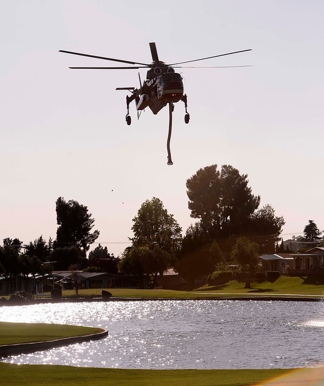 Description of . A helicopter draws water from a lake at the Highland Springs Country Club in Cherry Valley May 2, 2013.   GABRIEL LUIS ACOSTA/STAFF PHOTOGRAPHER.