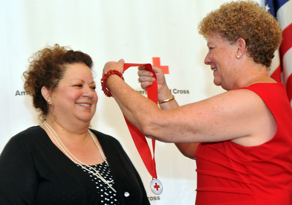 Description of . Julia Pacheco, of Pico Rivera, receives a medal from Mollie Beck as the Rio Hondo Chapter of the American Red Cross honors 14 people for their part in performing extraordinary acts during their Hometown Heroes luncheon at the Quiet Cannon in Montebello on Thursday June 27, 2013. (SGVN/Staff Photo by Keith Durflinger)