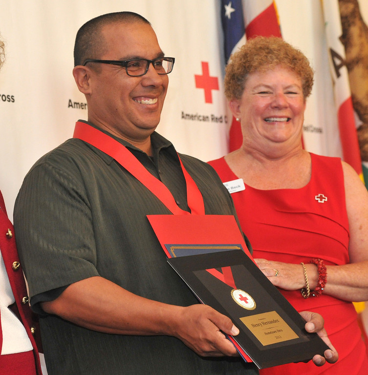 Description of . Bus driver Henry Hernandez receives a medal as  the Rio Hondo Chapter of the American Red Cross honors 14 people for their part in performing extraordinary acts during their Hometown Heroes luncheon at the Quiet Cannon in Montebello on Thursday June 27, 2013. (SGVN/Staff Photo by Keith Durflinger)