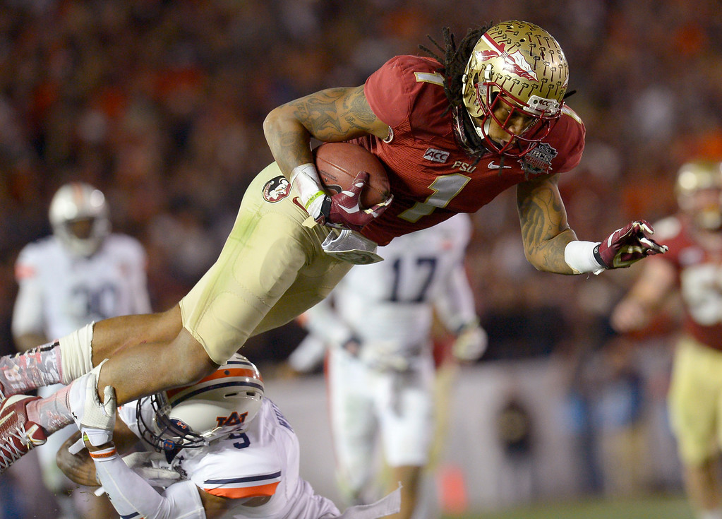 Description of . Florida State's Kelvin Benjamin is tackled by Auburn's Jermaine Whitehead after catching a pass during the 2014 Vizio BCS National Championship January 6, 2014 in Pasadena CA.  Florida State won the game 34-31.(Andy Holzman/Los Angeles Daily News)