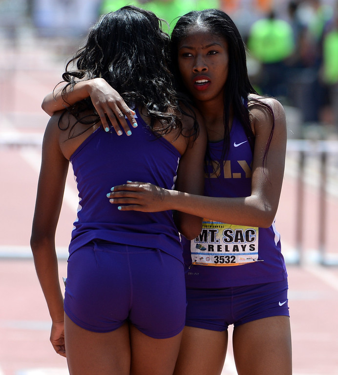 Description of . Long Beach Poly's Ebony Crear, left, is hugged by Kymber Payne after the 300 meter hurdles Invitational during the Mt. SAC Relays in Hilmer Lodge Stadium on the campus of Mt. San Antonio College in Walnut, Calif., on Saturday, April 19, 2014. 