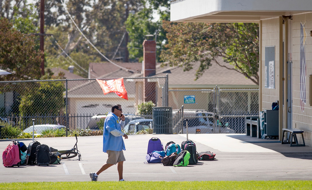 Description of . Longden Elementary School officials pick up abandoned student backpacks after Los Angeles County Sheriff's deputies responded to a bomb threat at the Temple City, Calif. campus Sept. 25, 2013.  (Staff photo by Leo Jarzomb/San Gabriel Valley Tribune)