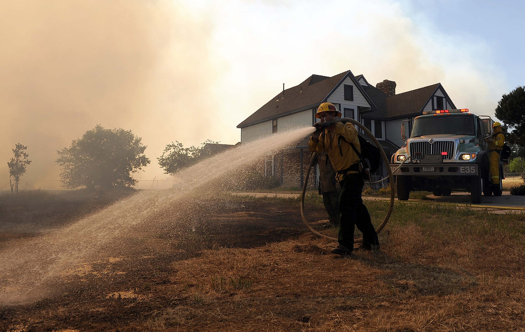 Description of . A U.S Forest Service firefighter battle flames near a home on a 1,500 acre brush fire Wednesday May 1, 2013 in Banning. LaFonzo Carter/Staff Photographer