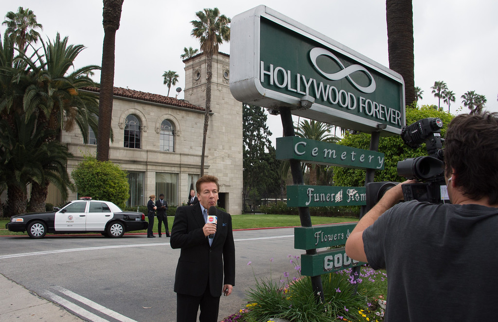 Description of . A TV journalist delivers  his report on the funeral of Mick Jagger's  late girlfriend  LWren Scott outside Hollywood Forever Cemetery in Hollywood, California on March 25, 2014.  The model-turned-fashion designer was found hanged in her luxury New York apartment last week. She was 49. The cemetery was closed for the roughly one-hour service, held amid tight security.           (JOE KLAMAR/AFP/Getty Images)