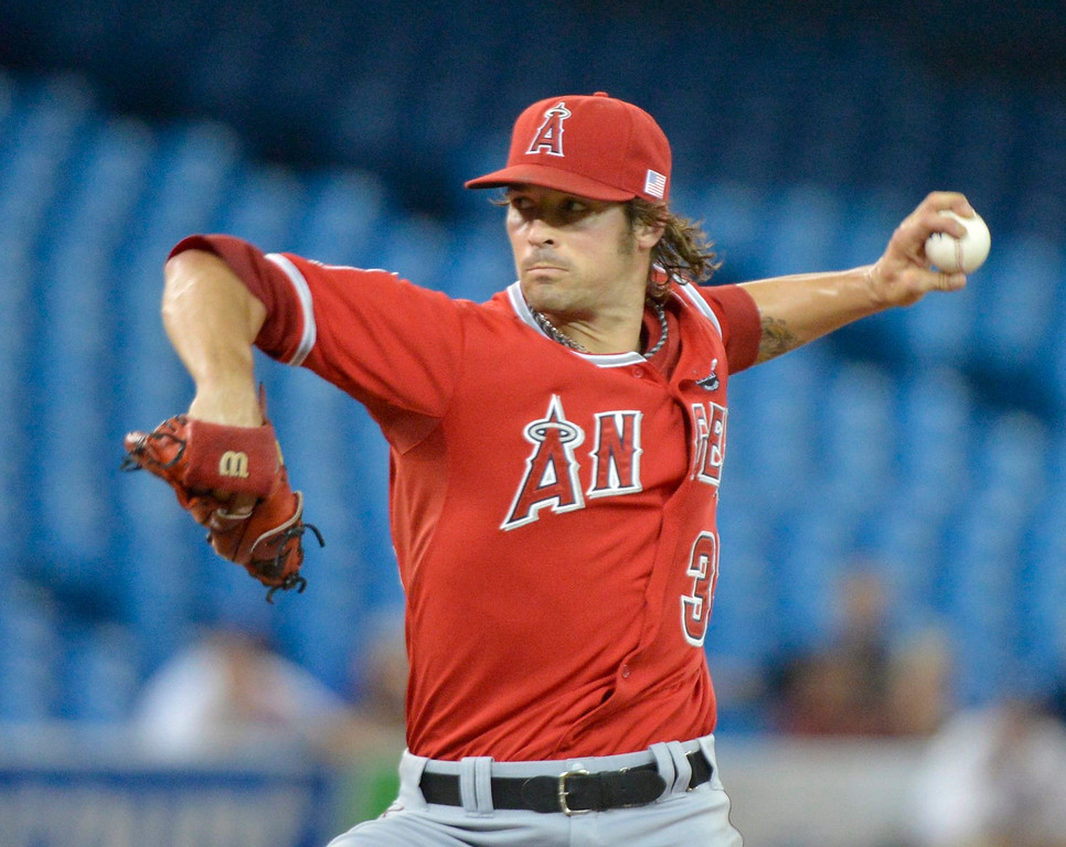 Description of . Los Angeles Angels starting pitcher C.J. Wilson throws against the Toronto Blue Jays during first-inning AL baseball game action in Toronto, Wednesday, Sept. 11, 2013. (AP Photo/The Canadian Press, Nathan Denette)