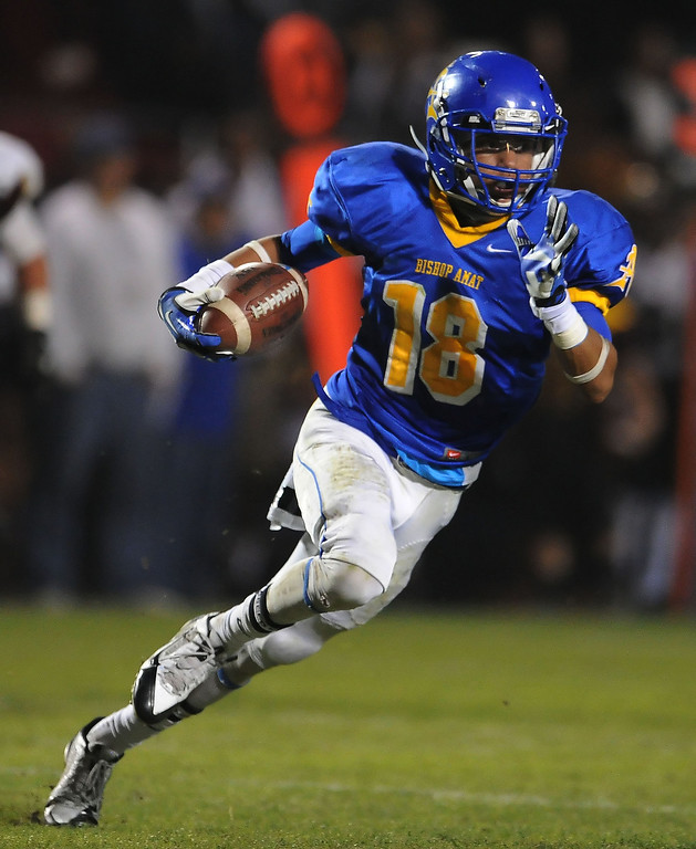 Description of . Bishop Amat's Trevon Sidney catches a pass for a first down against Alemany in the first half of a prep football game at Bishop Amat High School in La Puente, Calif., on Friday, Oct. 25, 2013.    (Keith Birmingham Pasadena Star-News)