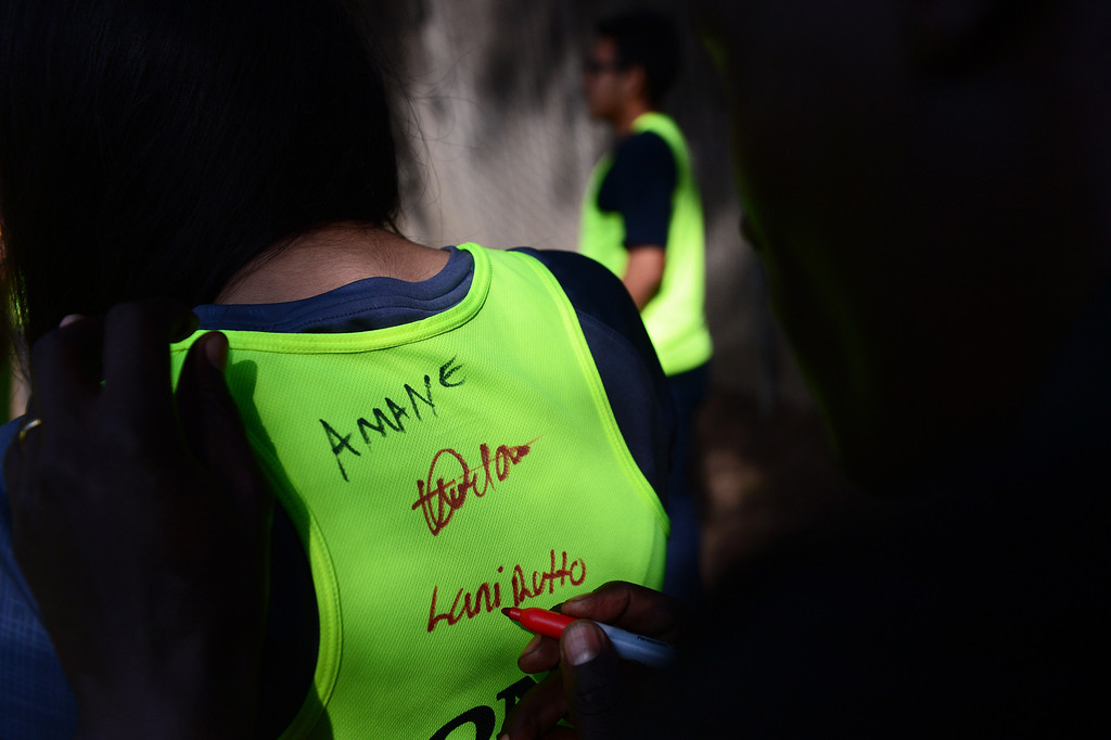 Description of . Elite marathon runner Lani Rutto, of Kenya, signs shoes and jerseys as elite marathon athletes visit with students of Students Run LA program during a training run for the LA Marathon at Griffith Park in Los Angeles Friday, March 7, 2014. The students will also be running Sunday's marathon. (Photo by Sarah Reingewirtz/Pasadena Star-News)