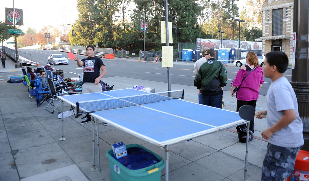 Description of . Fifteen year-old Dallas Teran, left, plays ping pong with tele year-old Devin Teran of Apple Valley as people camp out and stake their spots for the Rose Parade along Colorado Boulevard in Pasadena, Calif., on Tuesday, Dec. 29, 2013.     (Keith Birmingham Pasadena Star-News)