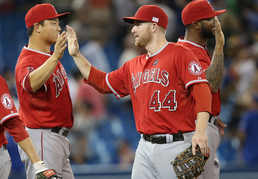 Description of . TORONTO, CANADA - SEPTEMBER 11: Mark Trumbo #44 of the Los Angeles Angels of Anaheim celebrates their victory with Hank Conger #16 during MLB game action against the Toronto Blue Jays on September 11, 2013 at Rogers Centre in Toronto, Ontario, Canada. (Photo by Tom Szczerbowski/Getty Images)