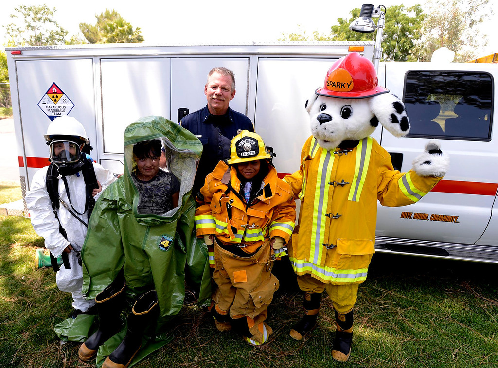 Description of . Brian Otter of San Bernardino County Fire/ Hazardous Material,center,  poses with students and mascot Sparky during the final day of the 19th Annual Career Awareness Week at Lankershim Elementary School in Highland June 6, 2013.  GABRIEL LUIS ACOSTA/STAFF PHOTOGRAPHER.