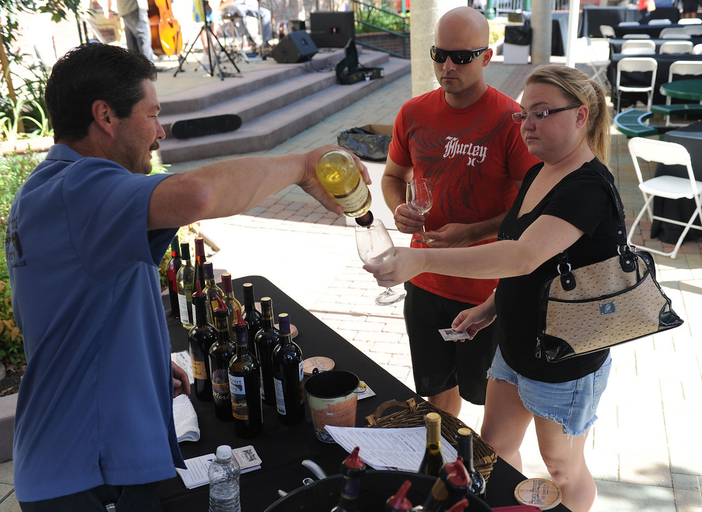 Description of . (John Valenzuela/ Staff Photographer)  Robin Harter of State Street Winery pours a glass of wine for Jessica Zimmerman and Gabriel Stearns of Grand Terrace during the Redlands Wine, Beer, and Music event at Ed Hales Park in downtown Redlands, Saturday, June 22, 2013.