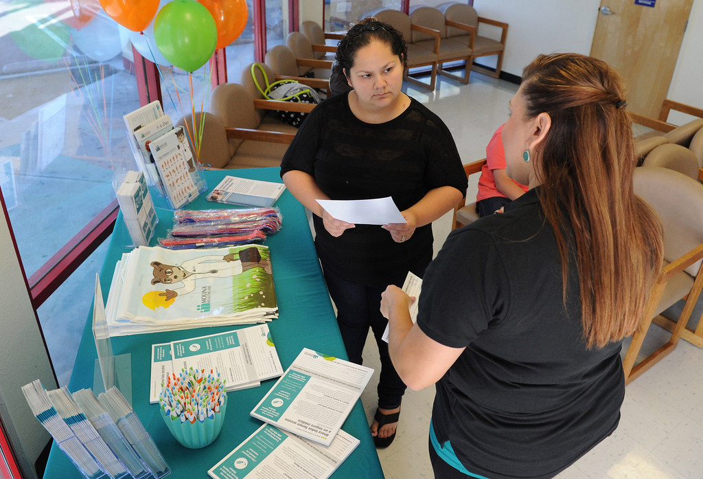 Description of . (John Valenzuela/Staff Photographer) Marisela Garcia of Rialto receives information about health insurance with Covered California from Ruthy Argumedo, associate vice president of community outreach for Molina Medical at Molina Medical in Fontana, Tuesday, Oct. 1, 2013. Today kick off the first day of open enrollment for Covered CA, the marketplace for affordable, private health insurance, Molina Medical  hosted an informational event for its patients and the Inland Empire community.