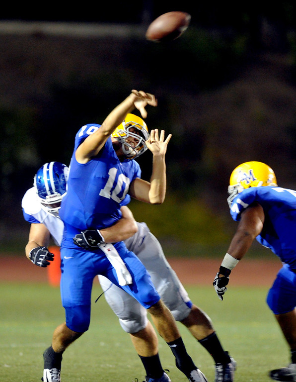 Description of . La Mirada quarterback Kevin Dillman (#10) gets hit by a La Habra defender as he throws a pass in their football game at La Mirada High School on Friday September 6, 2013. (Whittier Daily News/Staff Photo by Keith Durflinger)