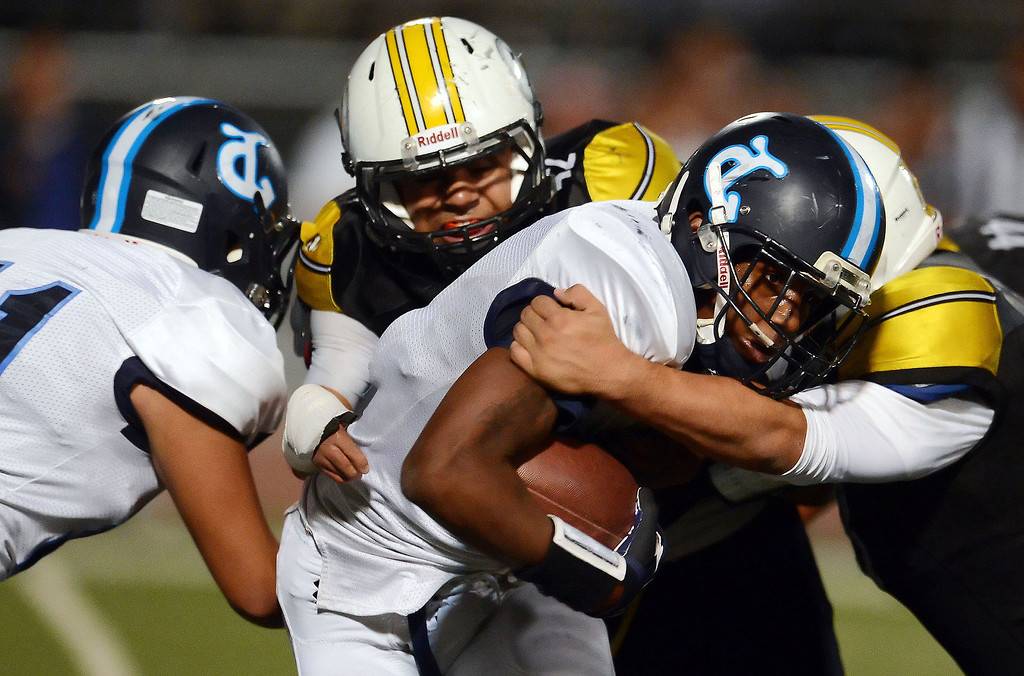 Description of . Duarte's Sam Edwards is tackled by the Bassett defense in the first half of a prep football game at Bassett High School in La Puente, Calif., on Friday, Nov. 1, 2013.    (Keith Birmingham Pasadena Star-News)
