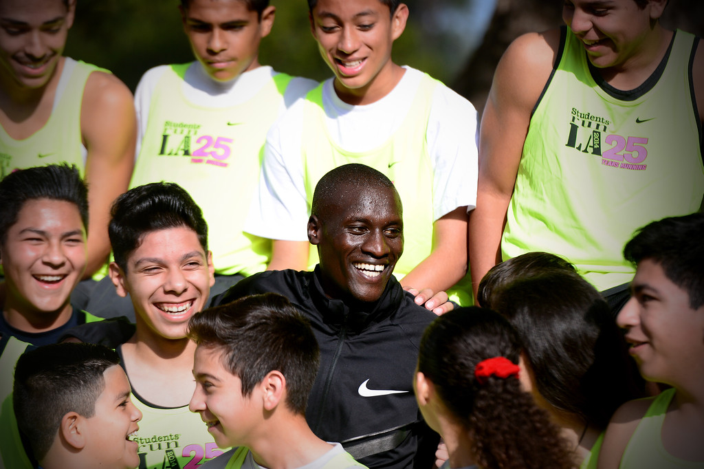 Description of . Elite marathon runner Lani Rutto, of Kenya, joins students, of the Students Run LA program, for a group portrait while the elite athletes were training at Griffith Park in Los Angeles Friday, March 7, 2014 for the LA Marathon. The students will also be running Sunday's marathon.(Photo by Sarah Reingewirtz/Pasadena Star-News)
