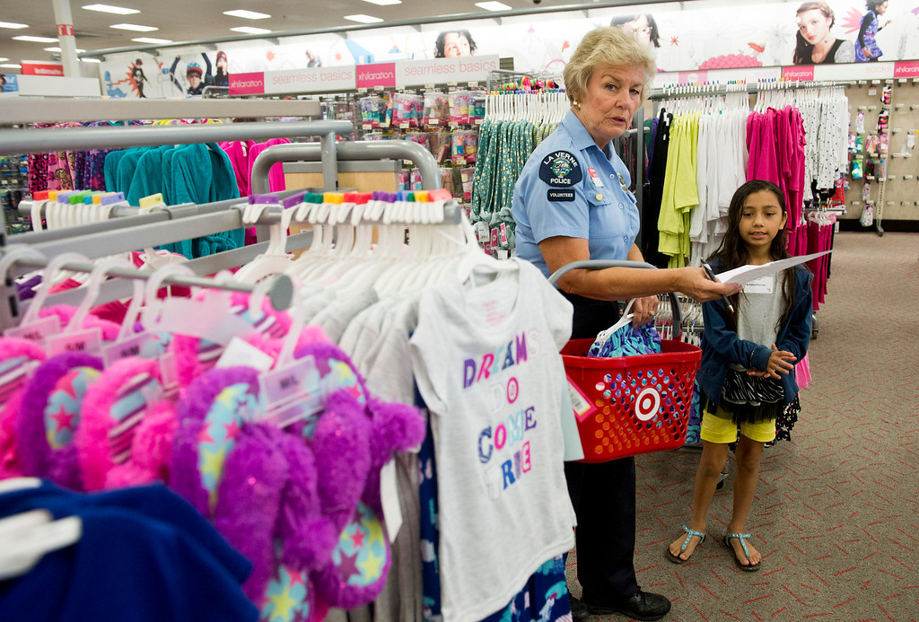 Description of . Volunteers from the Soroptimists club, as well as the RSVP (retired senior volunteer patrol) of La Verne PD, Los Angeles County Sheriff's Department and Los County firefighters all paired up with a student from Bonita Unified elementary to take them shopping and find clothes and shoes at Target in San Dimas on Tuesday, Sept. 10, 2013. (Photo by Watchara Phomicinda/ San Gabriel Valley Tribune)