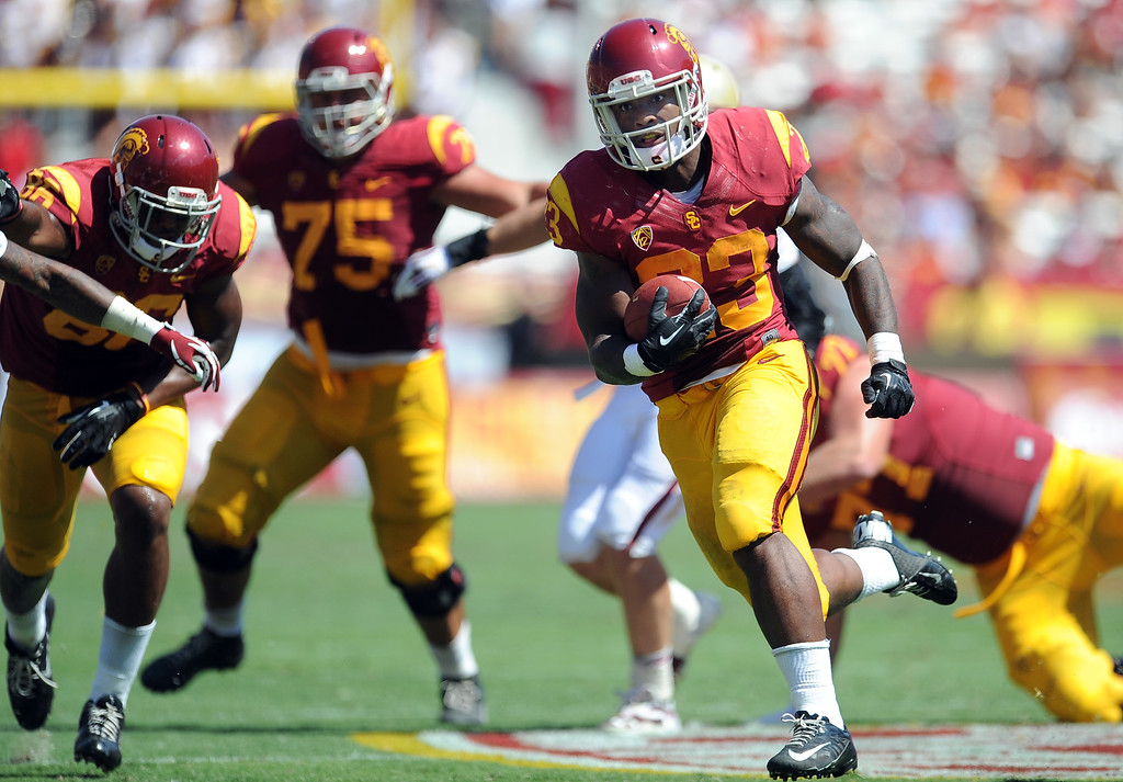 Description of . Southern California running back Tre Madden (23) runs for a 30 yard touchdown against Boston College during the second half of an NCAA college football game in the Los Angeles Memorial Coliseum in Los Angeles, on Saturday, Sept. 14, 2013. Southern California won 35-7. 