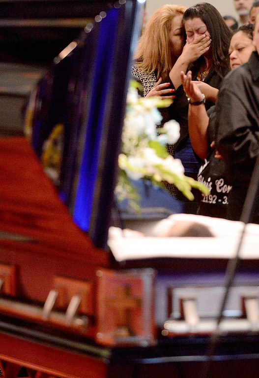 Description of . Loya Cotinola cries for her younger brother, Chris Cotinola Jr, during his funeral in Chino March 21, 2013. Chris Cotinola Jr., the 20-year-old Pomona man who was shot and killed outside his Gordon St apartment March 10. His was the third fatal shooting in the city since March 7. A total of four young men have lost their lives to gun violence.  (Staff photo by Thomas Cordova)