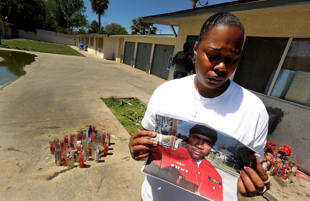 Description of . Ganesha Boone, 35, holds a picture of boyfriend Jerald Lee Belton at a memorial site along North Sierra Way in San Bernardino April 18, 2013.