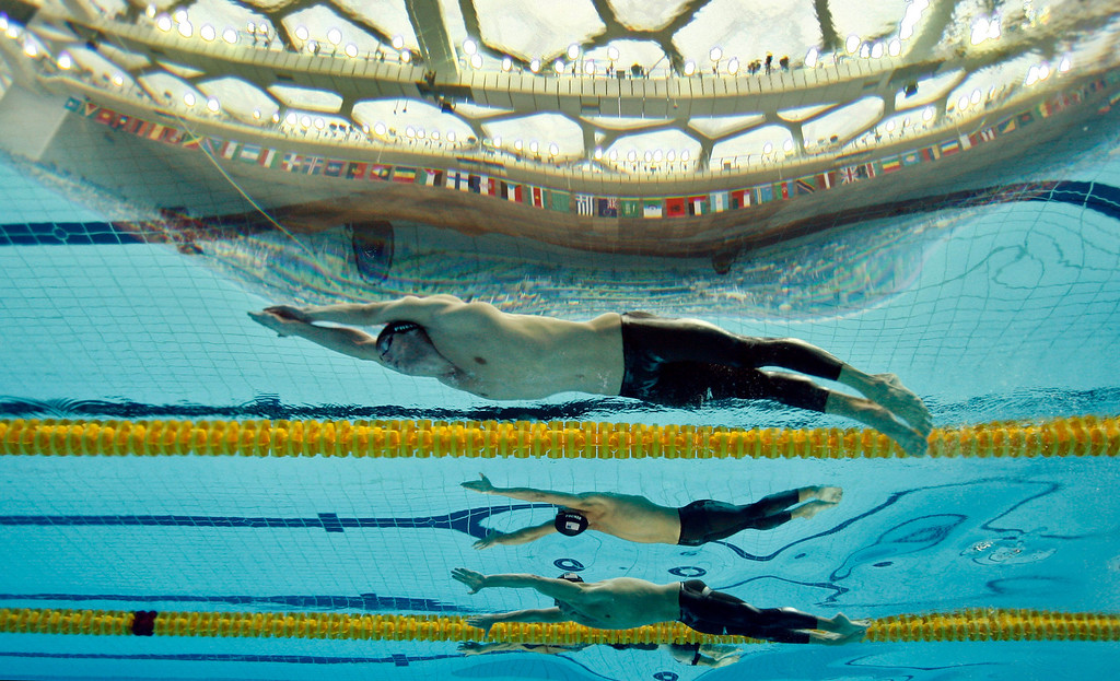 Description of . Beijing Olympics Swimming Mens Medleys  United States' Michael Phelps swims to the gold medal in the men's 200-meter individual medley final during the swimming competitions in the National Aquatics Center at the Beijing 2008 Olympics in Beijing, Friday, Aug. 15, 2008. In background is United States' Ryan Lochte, bronze. (AP Photo/Mark J. Terrill)