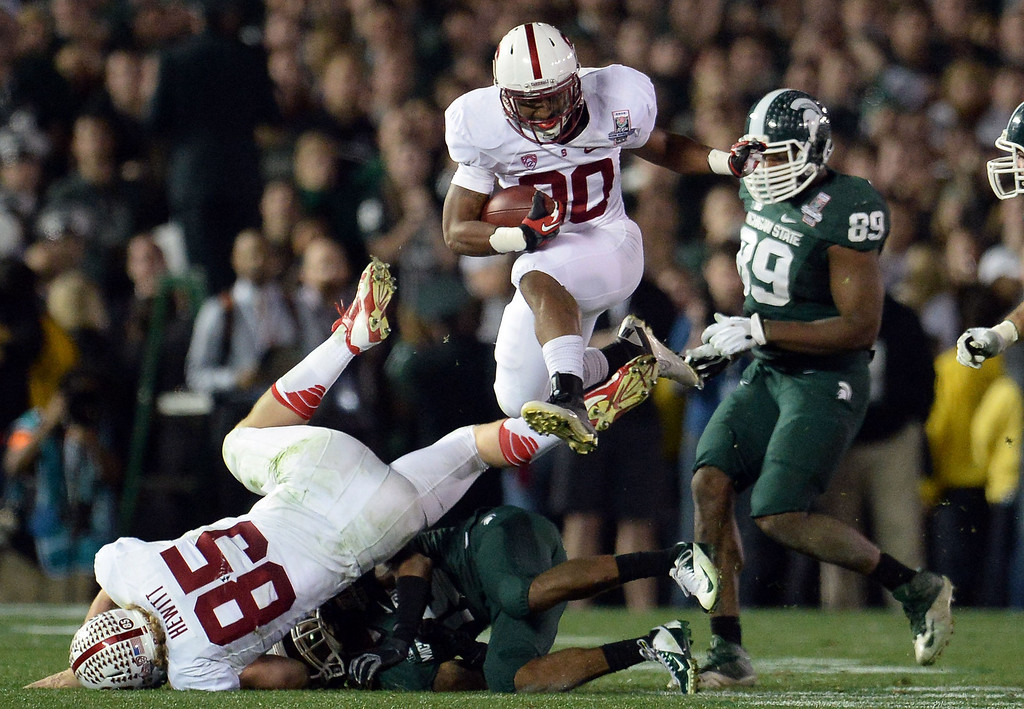 Description of . Stanford running back Ricky Seale (30) leaps over the Michigan State defense for a first down in the second half of the 100th Rose bowl game in Pasadena, Calif., on Wednesday, Jan.1, 2014. Michigan State won 24-20.