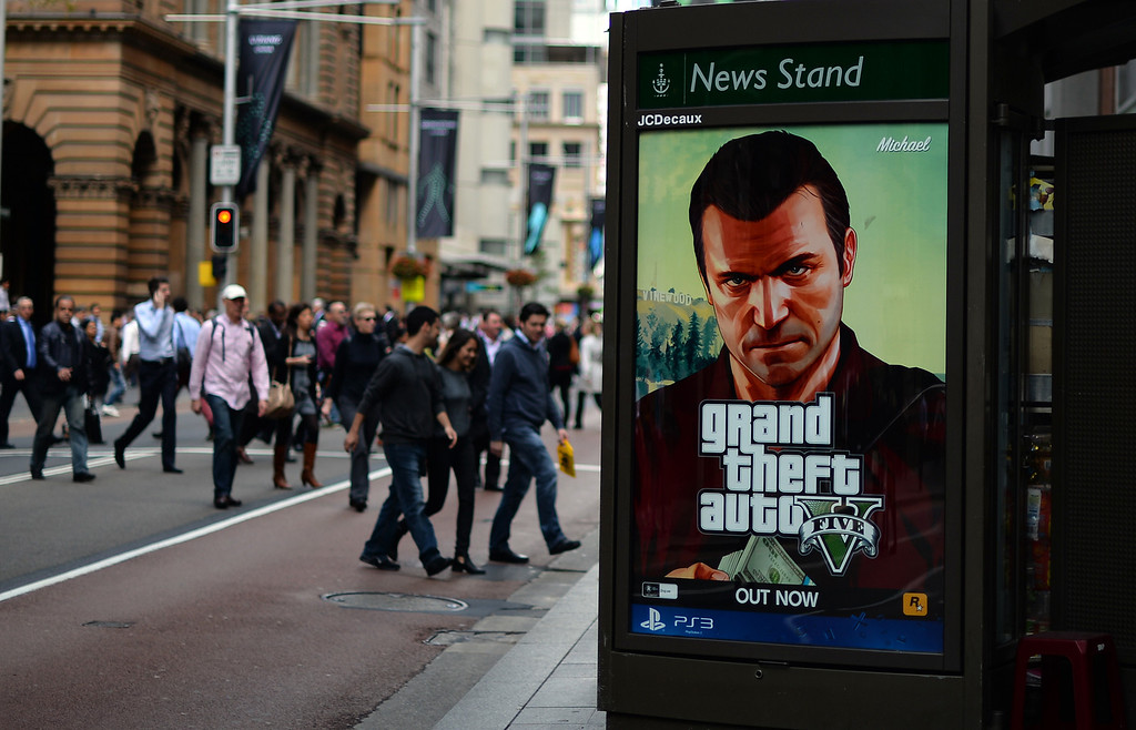 Description of . Commuters cross a main road next to an advertisement of console game Grand Theft Auto 5 in the central business district of Sydney on September 17, 2013. At midnight the doors of select games stores were opened for the launch of the much-awaited Grand Theft Auto 5 game in Australia.         (SAEED KHAN/AFP/Getty Images)