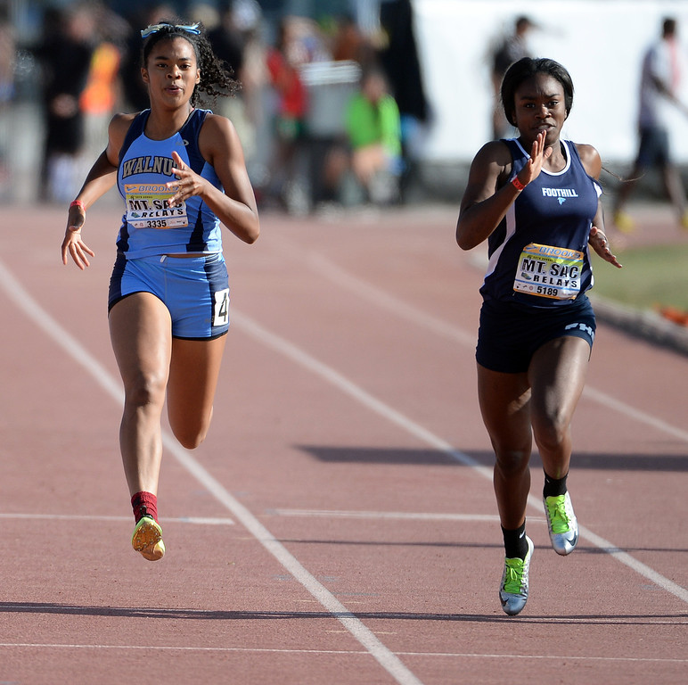 Description of . Walnut's Kayla Wilson, left, competes in the 200 Dash Invitational during the Mt. SAC Relays in Hilmer Lodge Stadium on the campus of Mt. San Antonio College in Walnut, Calif., on Saturday, April 19, 2014. 
