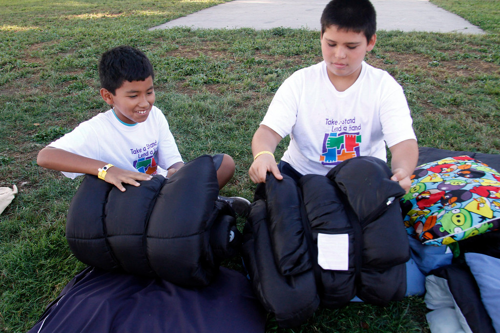 Description of . IDB-L-Pom-Campout-02 (Correspondent Photo by James Carbone) Joseph Diaz, 10, left, and Joseph Barajas, 10, roll up their sleeping bags, during the 2013 GREAT Camp Out, at the Park Square area at the Pomona Fairplex, in Pomona, Saturday, July 13, 2013. The Event organized by the Pomona Police Department provides an opportunity for kids to interact with police officers in a positive environment.