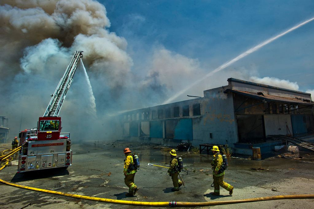 Description of . Los Angeles County firefighters battle a 3-alarm fire at an abandoned warehouse near 9th Avenue and Clark Avenue in City of Industry on Tuesday, July 9, 2013. (SGVN/Staff Photo by Watchara Phomicinda)