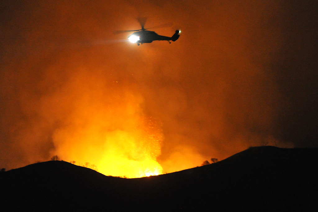 Description of . A Los Angeles County Fire Department water dropping helicopter flies over a ridge after making a night water drop to battle the Madre Fire in northwest of Highway 38 in Azusa on Monday September 23, 2013. (San Gabriel Valley Tribune/Staff Photo by Keith Durflinger)