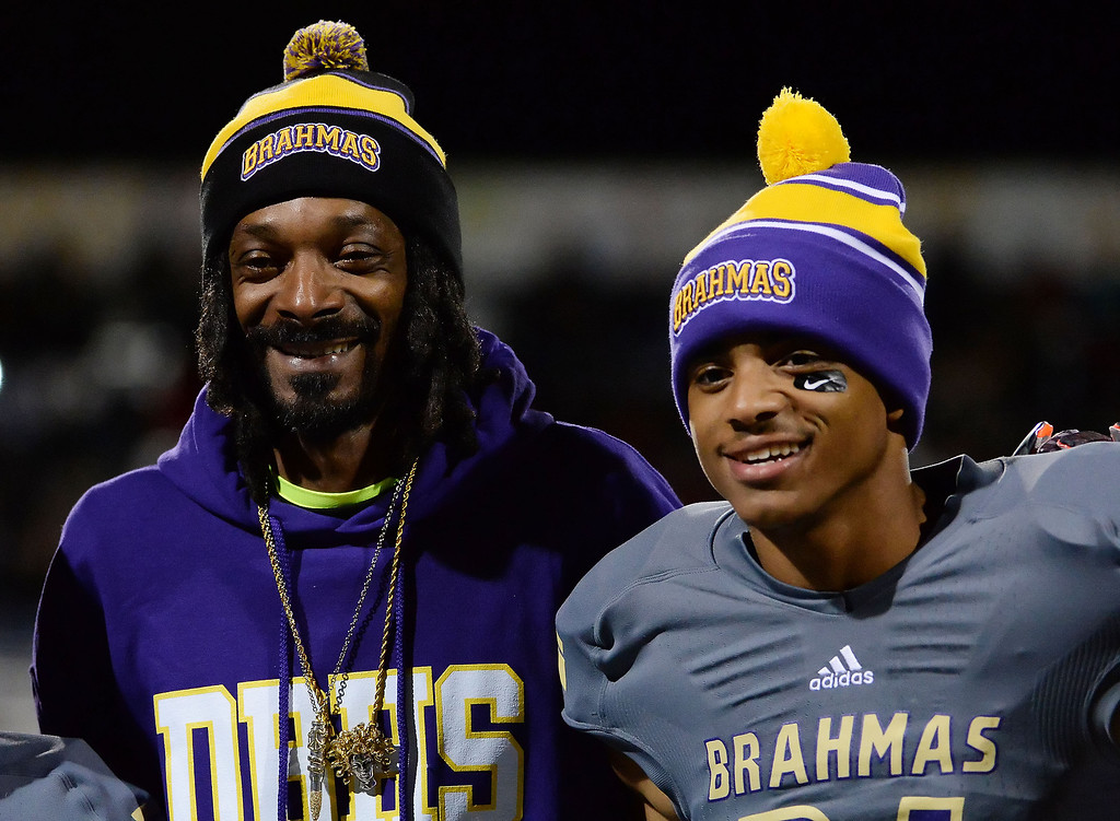 Description of . Snoop Dogg (Calvin Cordozar Broadus, Jr.) with his son Diamond Bar's Cordell Broadus poses for pictures on parents night prior to a CIF-SS playoff football game against La Serna at Diamond Bar High School in Diamond Bar, Calif., on Friday, Nov. 22, 2013.   (Keith Birmingham Pasadena Star-News)