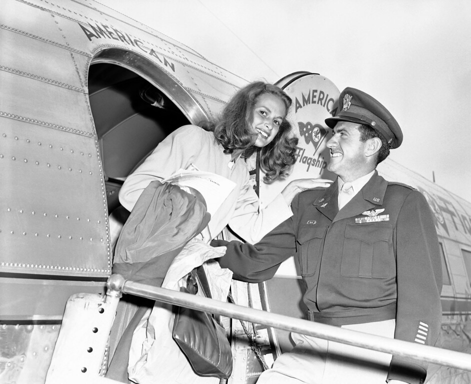 Description of . Capt. Lou Zamperini, former track star who survived 47 days on a life raft in the Pacific after the crash of his bomber, greets his bride-to-be, Miss Cynthia Applewhite, upon her arrival by air at Burbank, California, on May 16, 1946 from Miami Beach, Florida. They said they expected to be married in early fall. (AP Photo)