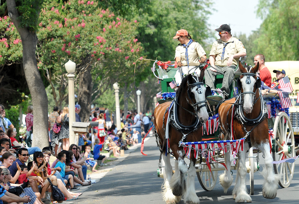 Description of . (John Valenzuela/Staff Photographer) Gray District Cub Scout Pack 5 make their way up Colton Ave. on a stagecoach during the Redlands Fourth of July Parade, Thursday, July 4, 2013.