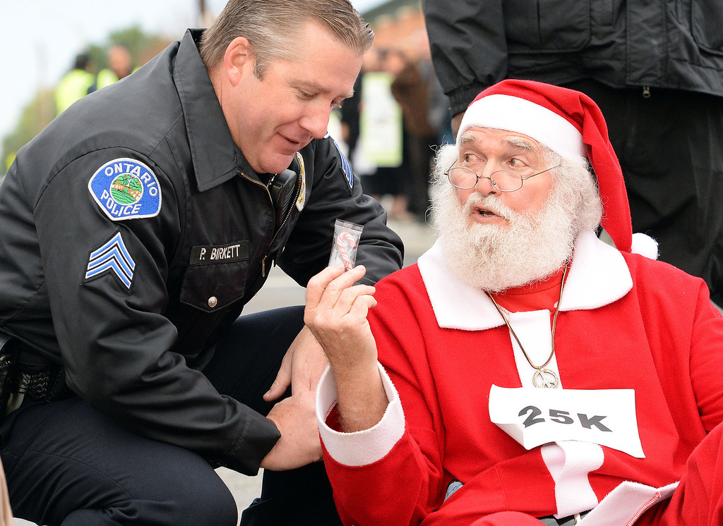 Description of . Walmart protester Karl Hilgert hands Ontario police department Sgt Pat Birkett a candy cane as Hilgert is read his rights before being arrested for failure to disperse after sitting down with 9 other protesters in the middle of the intersection at 5th and Mountain Avenues in Ontario Friday morning November 29, 2013. Over 100 protesters came to the Walmart on Mountain Avenue to protest against Walmart's wages and benefits.  (Staff photo by Will Lester)