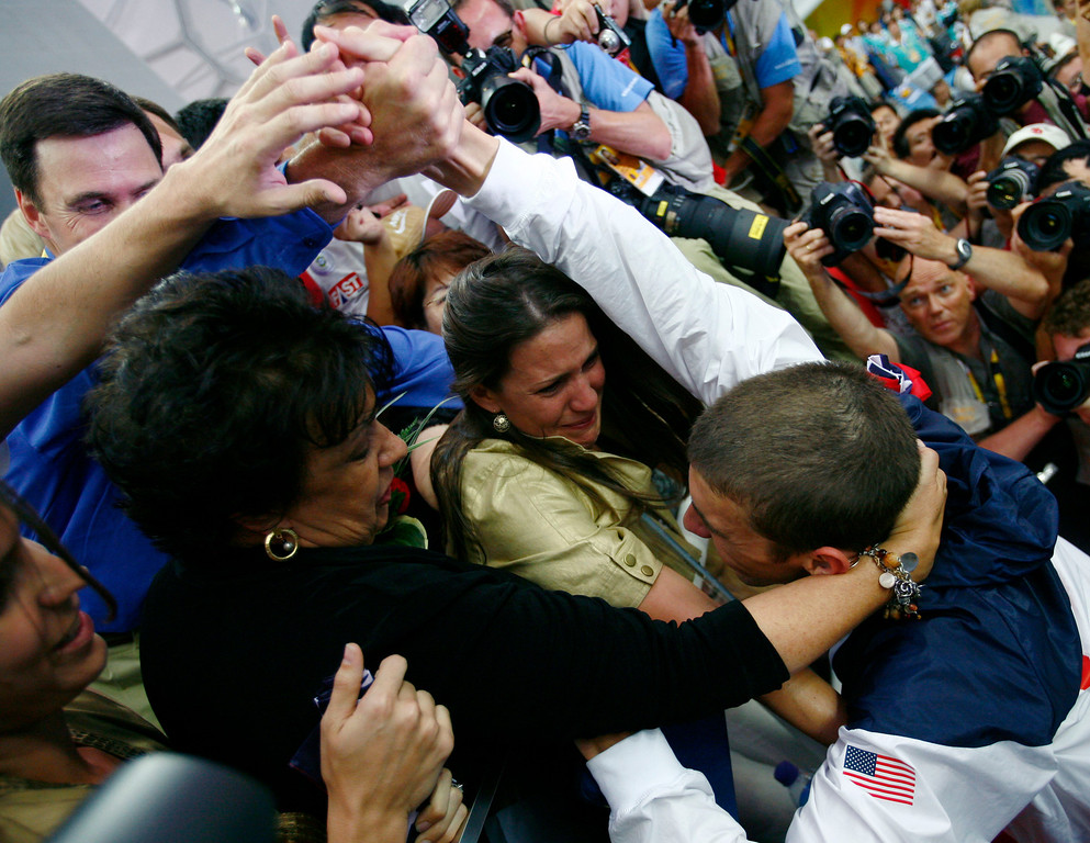 Description of . Michael Phelps of the United States goes to hug his mother Debbie, left, and other unidentified relatives after the medal ceremony for men's  4x100-meter medley relay final during the swimming competitions in the National Aquatics Center at the Beijing 2008 Olympics in Beijing, Sunday, Aug. 17, 2008. (AP Photo/Itsuo Inouye)