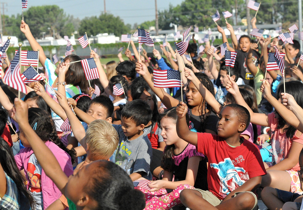 Description of . (John Valenzuela/Staff Photographer) Students from Mission Elementary School in Redlands, wave American Flags during the schools Patriot's Day celebration on the 12th Anniversary of the 9/11 attacks, Wednesday, September 11, 2013. Military veteran Robert Kafader discussed the tragic events that happen on Sept. 11, 2001, when nearly 3000 people were killed during the terrorist attacks 12 years ago.