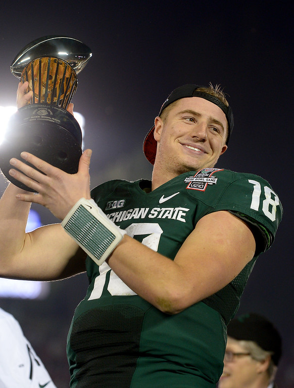 Description of . Michigan State quarterback Connor Cook holds up the trophy after beating Stanford 24-20 at the Rose Bowl, Wednesday, January 1, 2014. (Photo by Michael Owen Baker/L.A. Daily News)