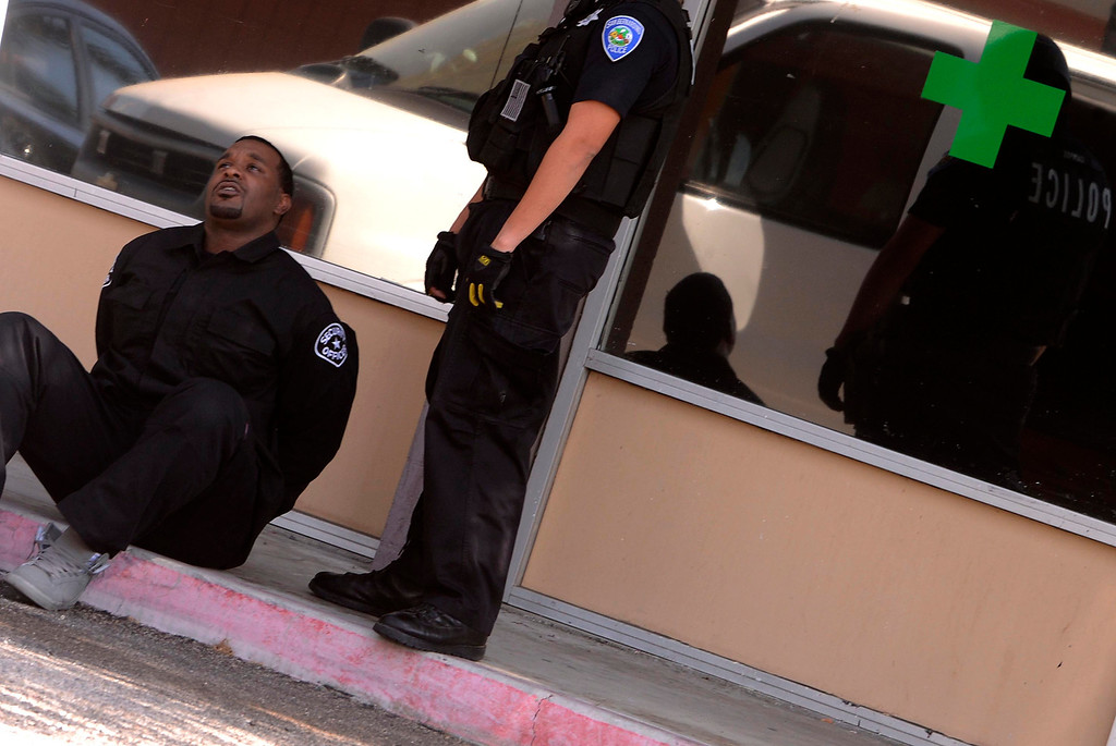 Description of . San Bernardino Police officers detain a security guard of the S.B.P.C. medicinal marijuana dispensary during a bust in San Bernardino May 29, 2013.  The City of San Bernardino continued its ongoing effort to close all dispensaries in the city with more busts today. (Photo by Gabriel Luis Acosta/The Sun)