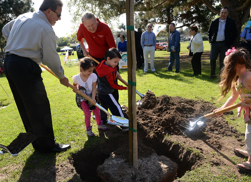 Description of . City council members Fernando Dutra, left and Mayor Bob Henderson help school children, from left, Sofia Altimirano, Justin Alvarado and Zoe Leal plant a tree during the Annual Arbor Day celebration at Michigan Park in Whittier on Thursday March 13, 2014. Children were able to help plant trees, see demonstrations by city workers and see information booths from area conservation groups. (Staff Photo by Keith Durflinger/Whittier Daily News)