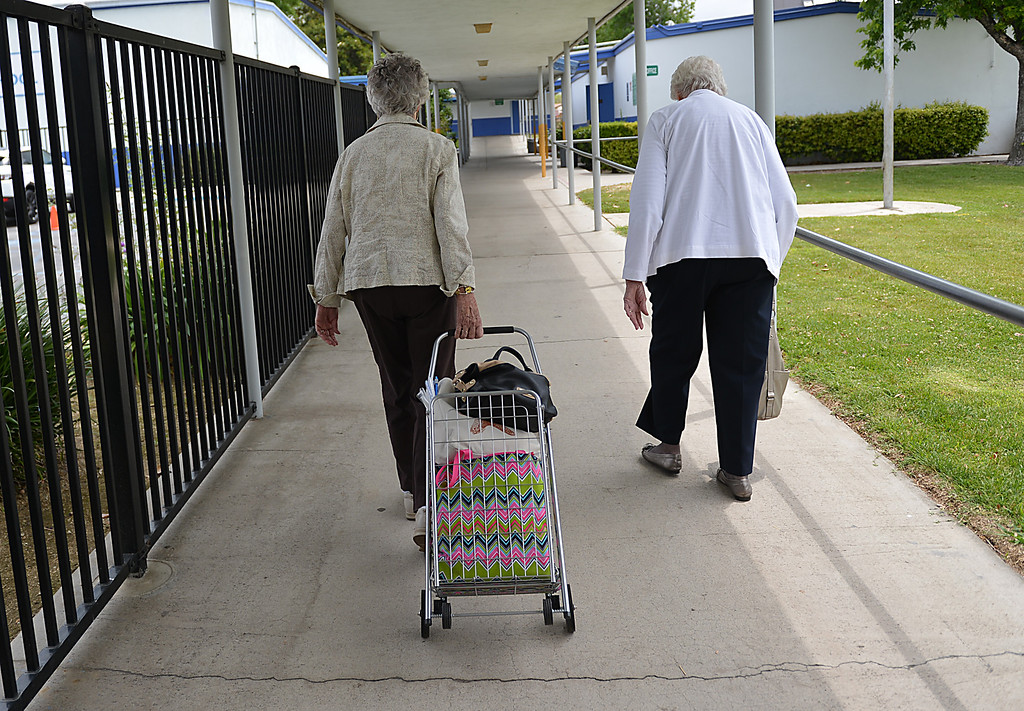 Description of . Barbara Ferguson, left and Pearl Koninig make their way toward the Lugonia School Crochet Club where they teach fifth graders the art of crocheting. Twice a week, for the past six years, fifth-graders at Lugonia Elementary School in Redlands have spent their lunch time crocheting. The