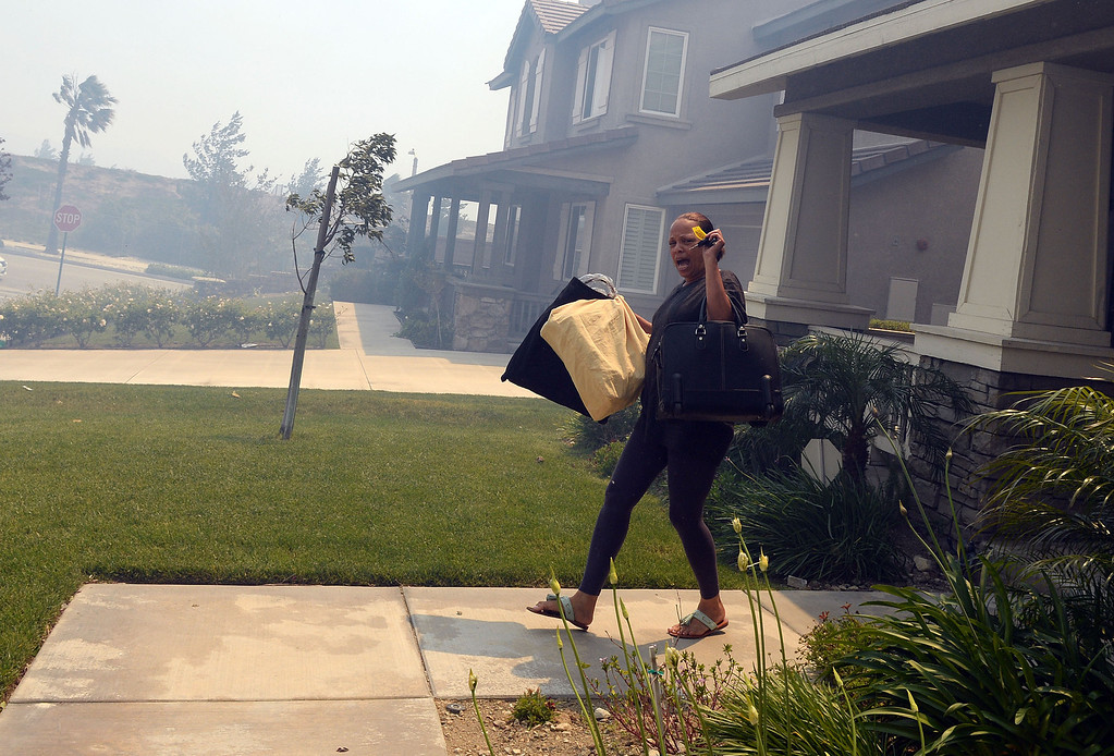 Description of . A resident evacuates with items from her home Wednesday in Rancho Cucamonga. Over 1000 acres and over a 1,000 homes are under mandatory evacuation as the Etiwanda Fire burns in Rancho Cucamonga Wednesday April 30, 2014. Cause of the fire is unknown and is burning in areas which burned during the Grand Prix Fire in October 2003. (Will Lester/Inland Valley Daily Bulletin)
