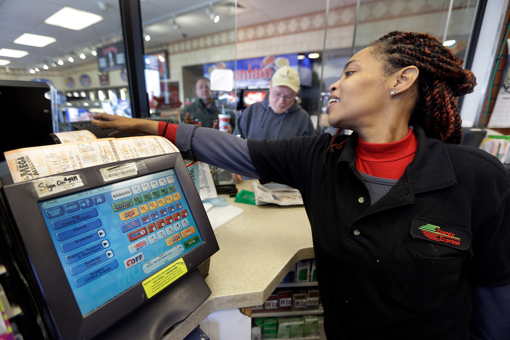 Description of . Energy Express assistant manager Anita Watson, right, sells a Mega Millions lottery ticket to Brian Thomason Monday, Dec. 16, 2013, in St. Louis. The Mega Millions jackpot now stands at an estimated $586 million and could rise before the next drawing set for Tuesday night. (AP Photo/Jeff Roberson)